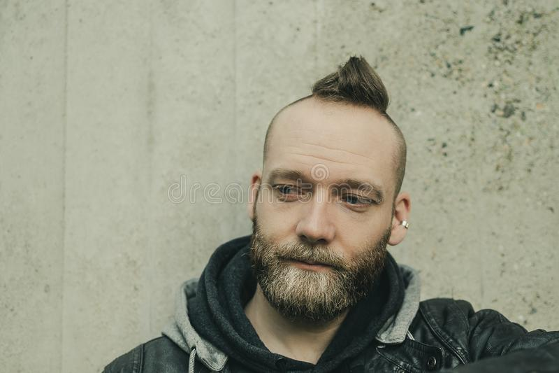 A man with mohawk is looking down in front of the camera stock image