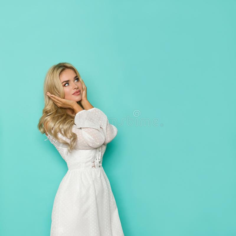 Thinking Beautiful Blond Woman In White Dress Is Holding Head In Hands And Looking Up stock photography