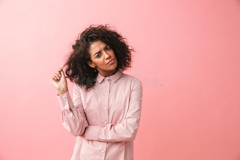 Thinking beautiful young african woman posing isolated over pink wall background dressed in pajama stock image