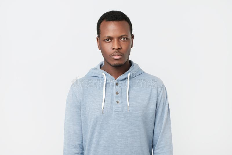African man with serious expression looking at camera while posing against white studio wall. stock photo