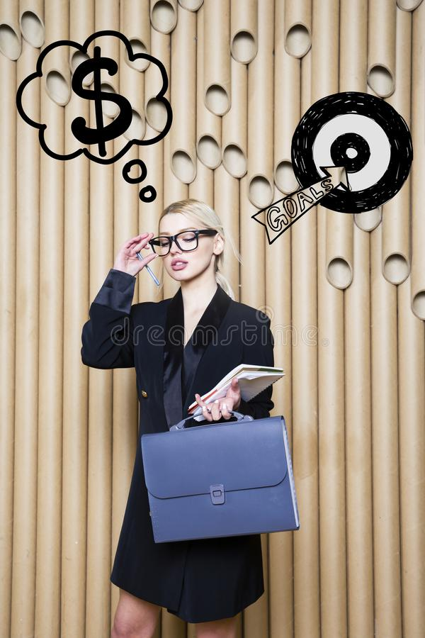 Thinking woman looking up on money sign in bubble and sketch target. Money concept on design background with lamps. Thinking blond woman looking up on money royalty free stock image
