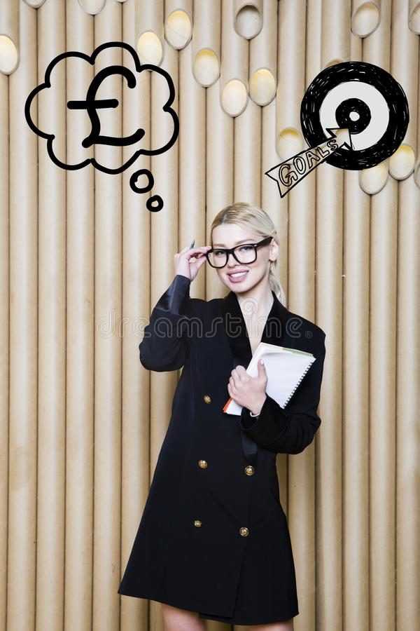Thinking woman looking up on money sign in bubble and sketch target. Money concept on design background with lamps. Thinking blond woman looking up on money royalty free stock photo