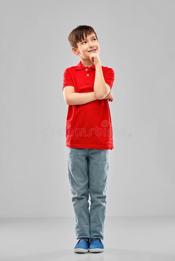 Thinking boy in red polo t-shirt. Childhood, expressions and people concept - smiling little boy in red polo t-shirt thinking over grey background stock photos