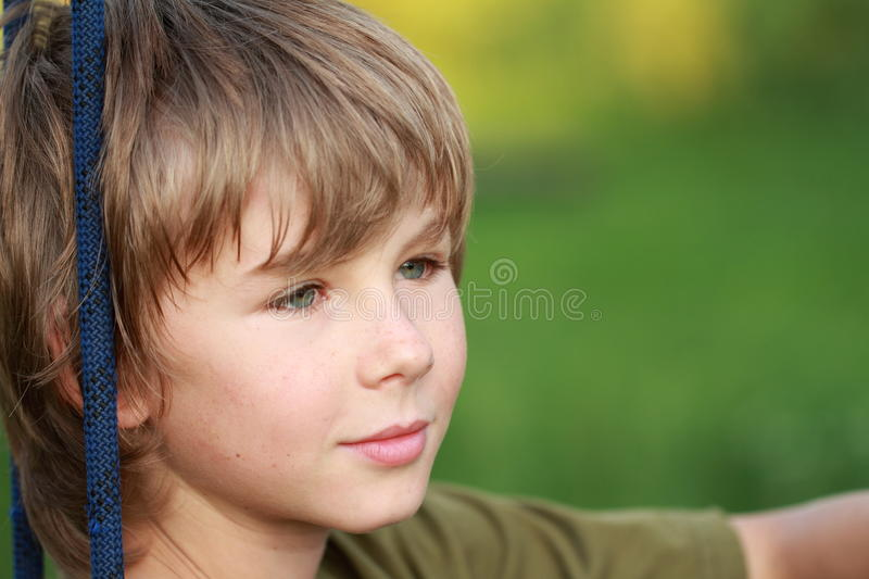 Thinking boy with smile. Face of a little boy with soft smile being thinking royalty free stock photo