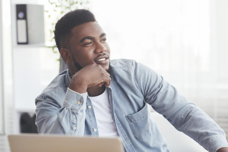 Portrait of pensive black businessman sitting at workplace in office stock photography