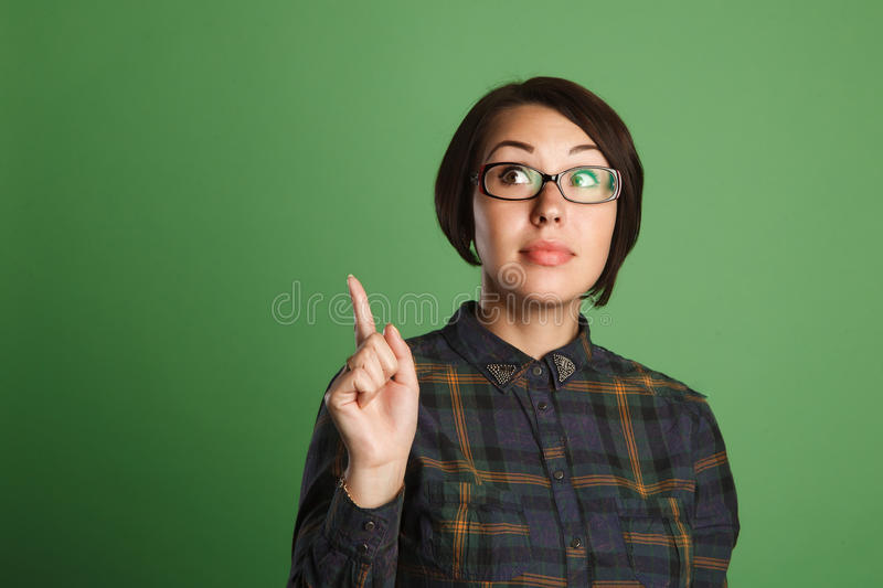 Thinking business woman with idea on green background.  royalty free stock image