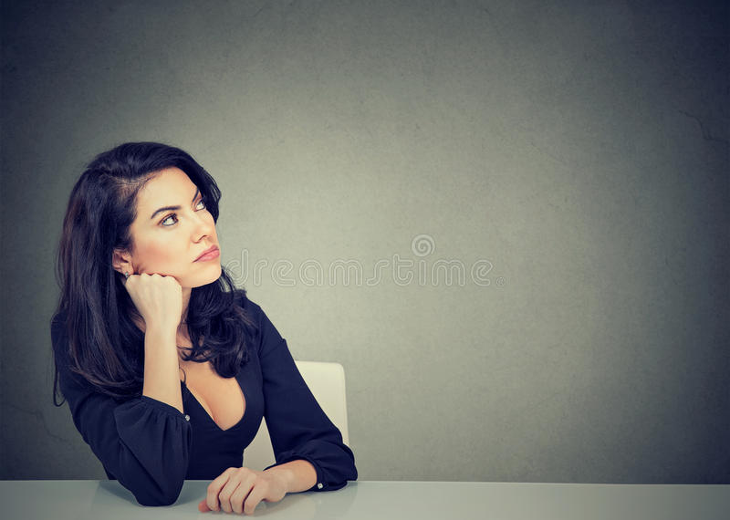 Thinking business woman sitting at desk stock photo