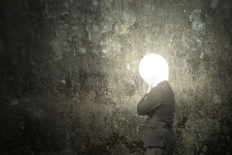 Thinking businessman with lamp head illuminated dark mottled con stock photography