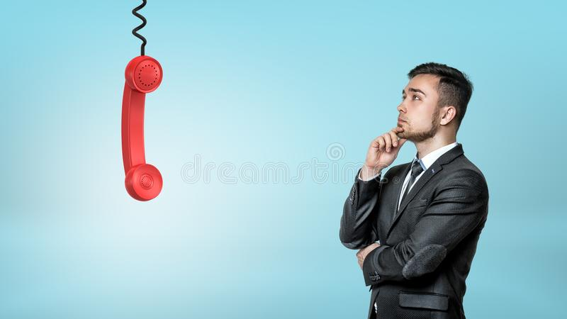 A thinking businessman looks up on a red retro phone receiver hanging from a black cord. stock photos