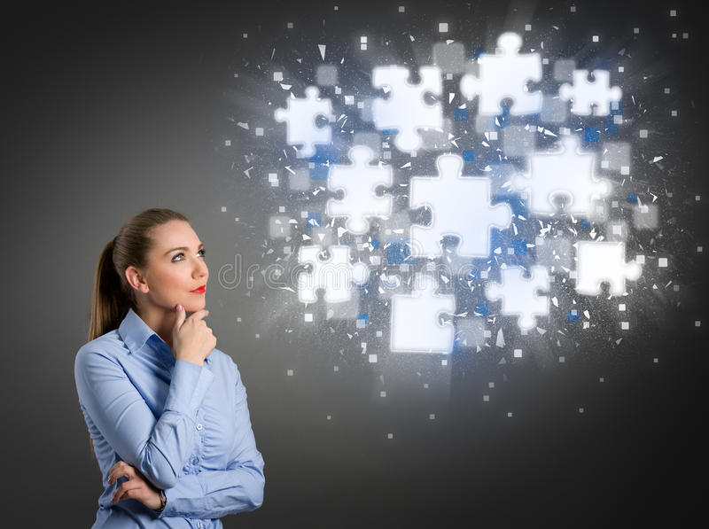 Thinking businesswoman looking at shining puzzle pieces royalty free stock images