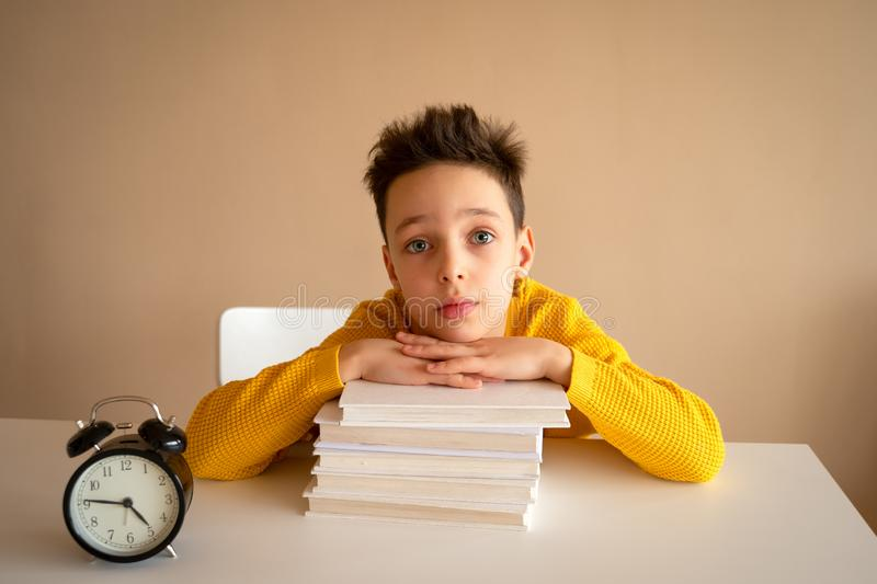 Thinking child bored, frustrated and fed up doing his homework stock photos