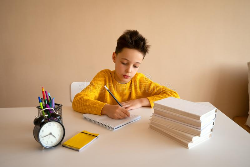 Thinking child bored, frustrated and fed up doing his homework stock images