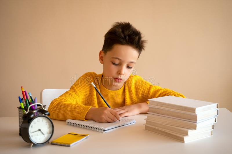 Thinking child bored, frustrated and fed up doing his homework royalty free stock photography