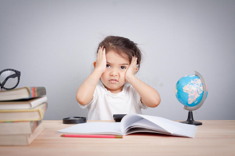 Thinking child bored, frustrated and fed up doing homework.  stock images