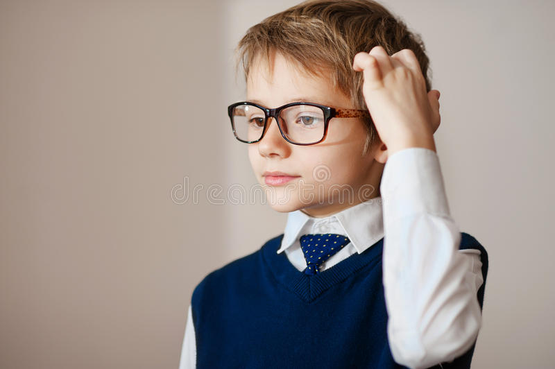 Thinking child portrait of a little boy age seven in glasses deeply about something looking up copy space above his hea. Thoughtful young schoolboy wearing royalty free stock photography