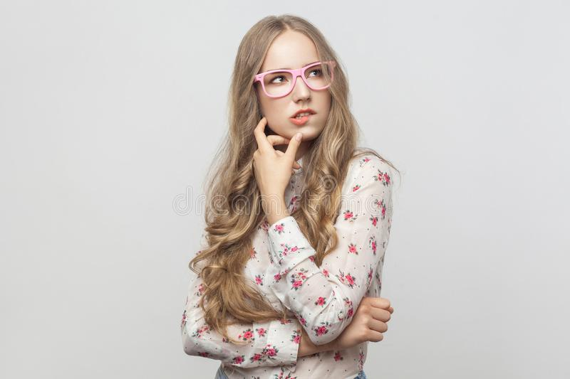 Thinking concept. Puzzlement long haired blonde woman in pink eyeglasses, touching her chin and looking up. Studio shot. Isolated on gray background stock photography