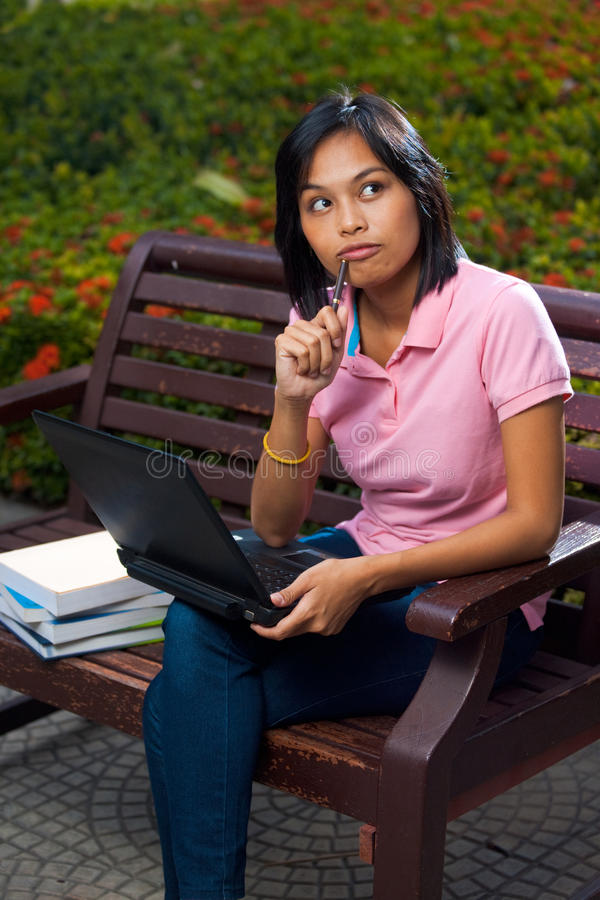 Thinking Cute College Student Bench Laptop. A cute college student thinking with a pen pressed against her mount on a university campus bench. 20s female Asian stock image