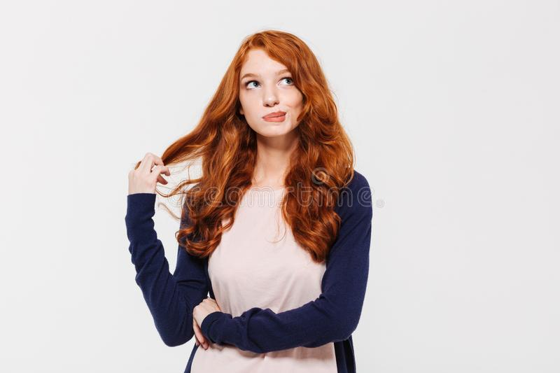 Thinking cute young redhead lady royalty free stock photos
