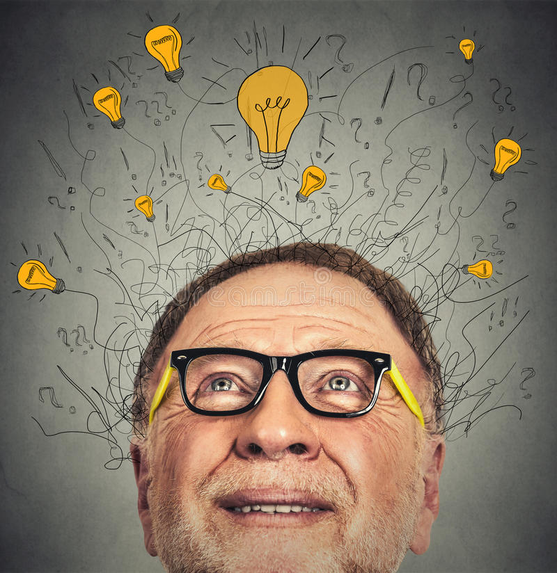 Thinking elderly man with question signs and light idea bulb above head. Looking up on gray wall background stock photos