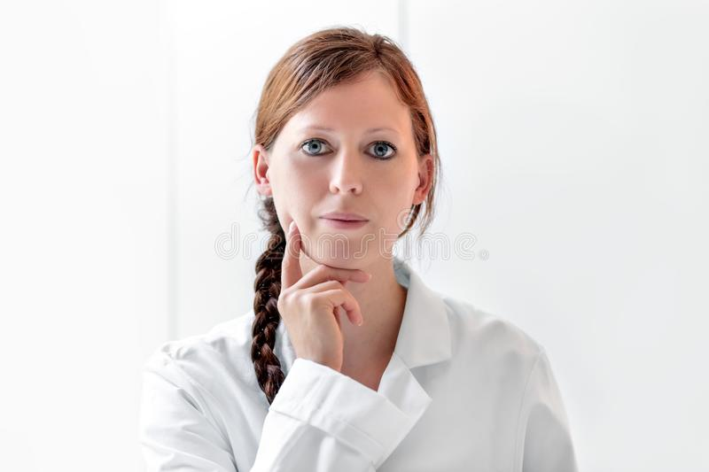 Thinking female doctor or nurse in front of white background, co stock photo