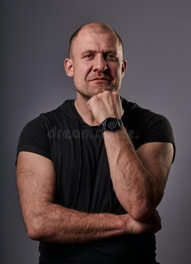 Thinking fun smiling bald man with folded arms in black casual shirt looking up on grey background. Closeup. Thinking fun smiling bald man with folded arms in royalty free stock photo