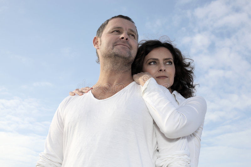 Thinking about future to come. Beautiful couple gazing into the distance with sky background royalty free stock photo