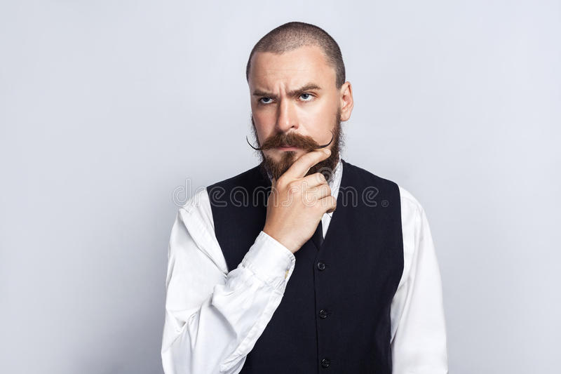 Thinking. Handsome businessman with beard and handlebar mustache looking and thinking. Studio shot, on gray background stock photography