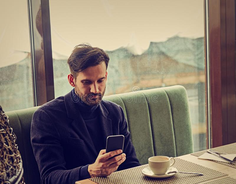 Thinking handsome man sitting in cafe drinking coffee and looking in mobile phote holding in the hand. Closeup stock photos