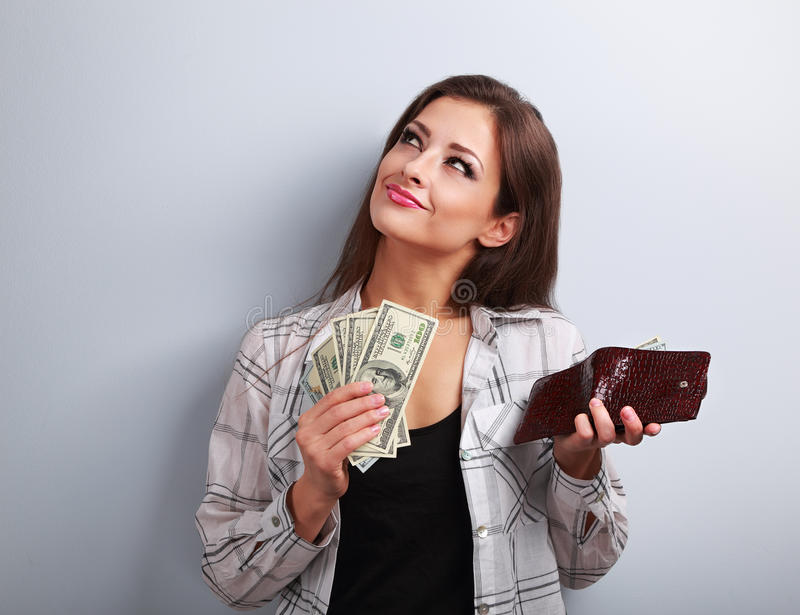 Thinking happy woman holding dollars and wallet in hands and wan. T to spend money on blue background stock images