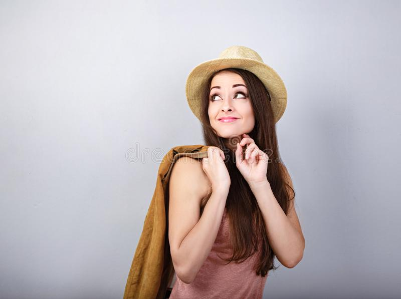 Thinking happy woman in pink  t-shirt and suumer straw hat holding leather jacket and looking up on blue background. Closeup stock photos