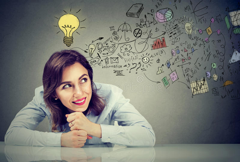 Thinking happy young business woman sitting at desk planning stock photo