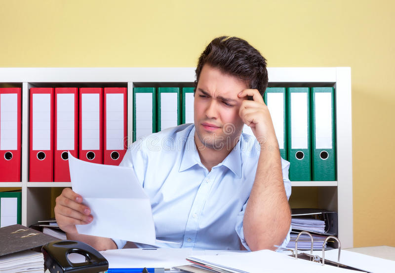 Thinking hispanic guy at office with a letter in his hand stock photo