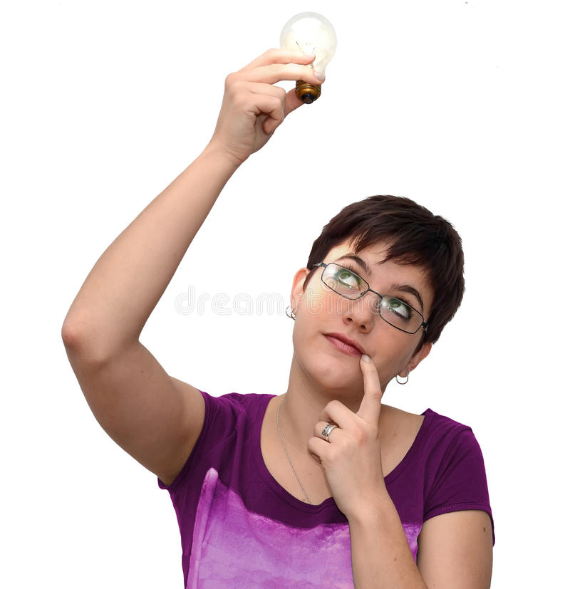 Thinking on an idea. Young woman looking at a lighted electric bulb in her hand, as if thinking on an idea royalty free stock photography