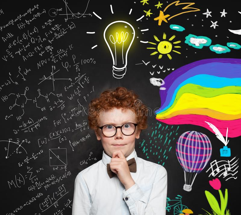 Thinking kid boy on blackboard background. Brainstorming, inspiration, creativity and idea concept.  royalty free stock photos