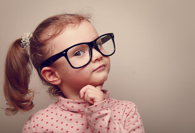 Thinking kid girl in glasses looking happy royalty free stock images