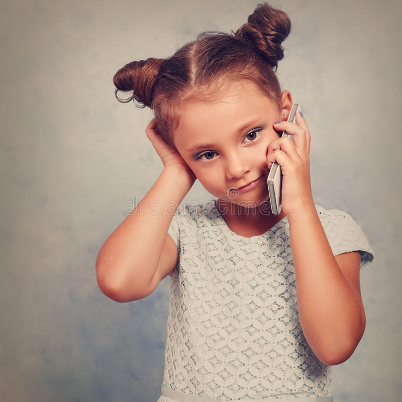 Thinking kid girl talking on mobile phone with happy smile on bl royalty free stock image