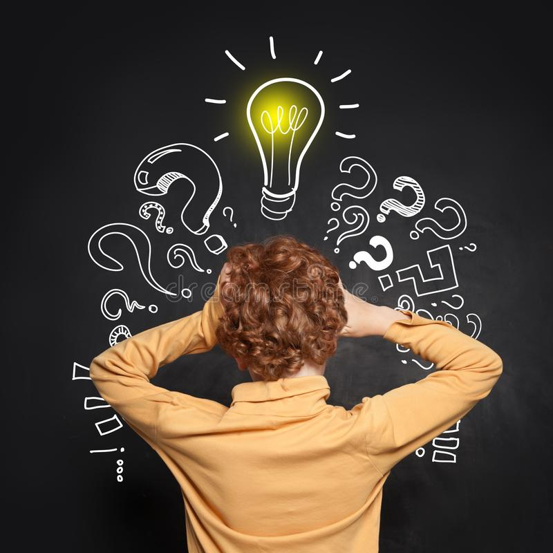 Thinking kid with lightbulb and question marks. Brainstorming and idea concept.  stock photos