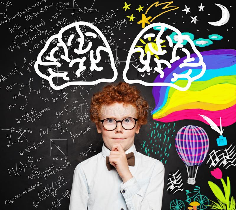 Thinking kid in white shirt and glasses on blackboard background with bright brain sketch drawn. royalty free stock images