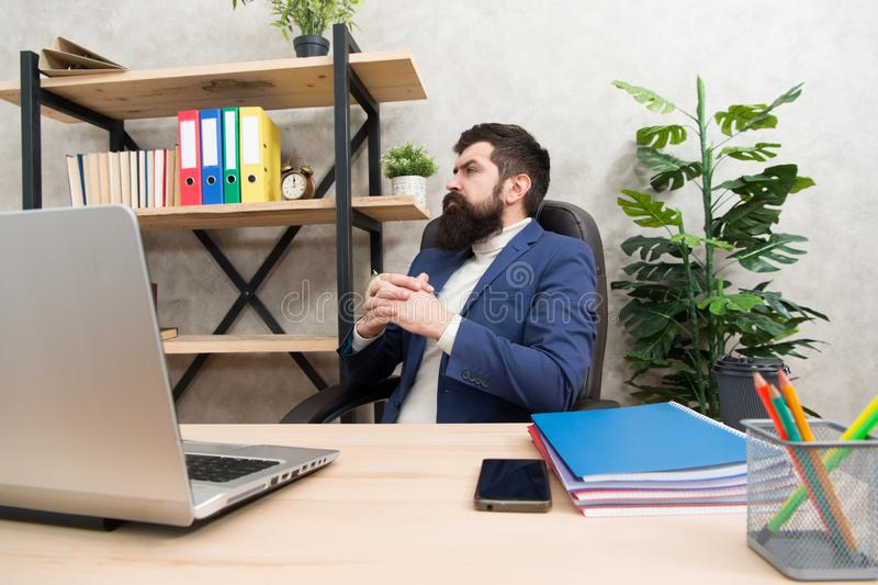 Thinking about main goal. Man bearded boss sit office with laptop. Manager solving business problems. Businessman in royalty free stock photo
