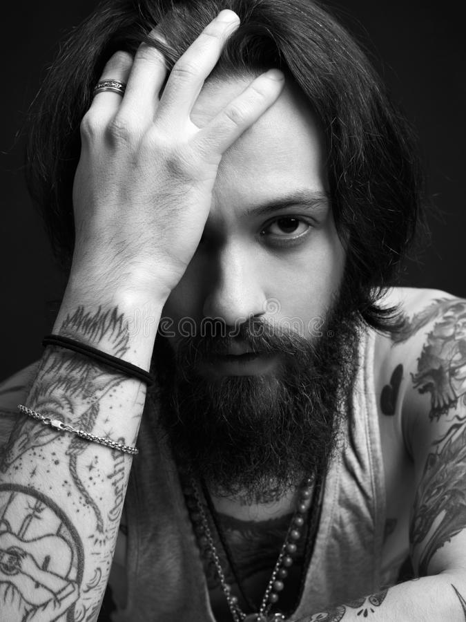 Thinking man with beard and tattoo. Bearded hipster boy black and white portrait royalty free stock photography