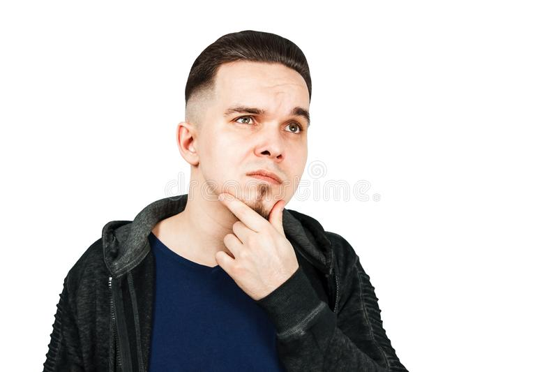 Thinking man holds hand at face, isolated on white background. Closeup portrait of young pensive guy. Caucasian male model royalty free stock images