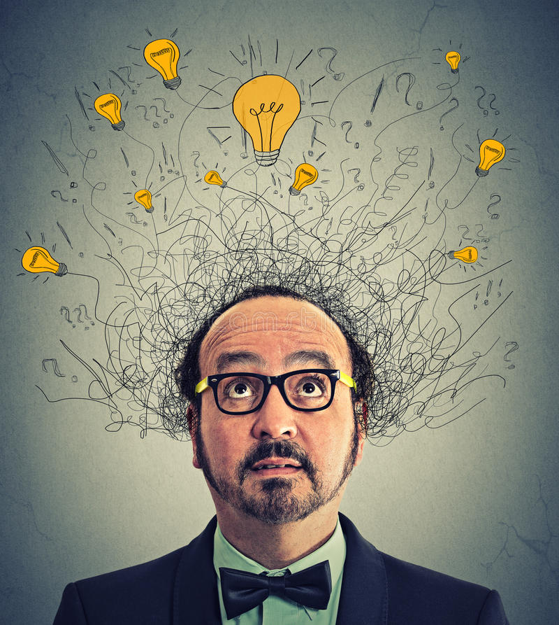 Thinking man with question signs and light idea bulbs above head. Looking up on gray wall background stock photography