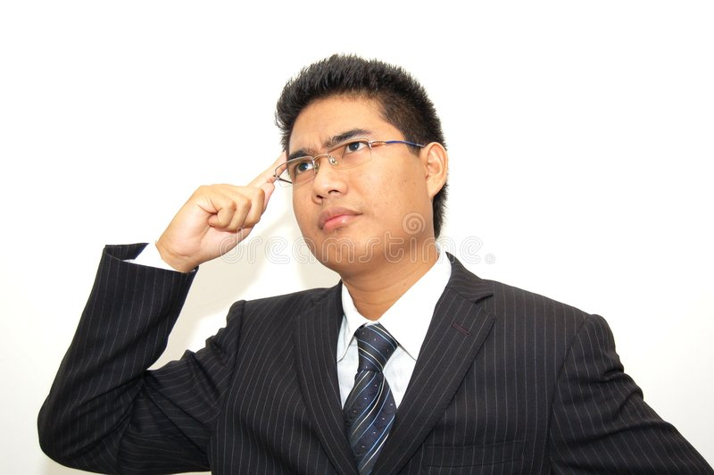 Thinking of New Idea. A young executive in suit thinking of a new idea, his finger point to head stock photos