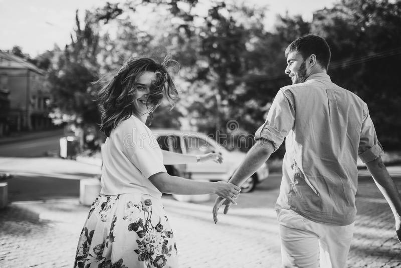 Thinking about new place to go. Beautiful young smiling couple hold hands each other and hurry to thier car royalty free stock photo