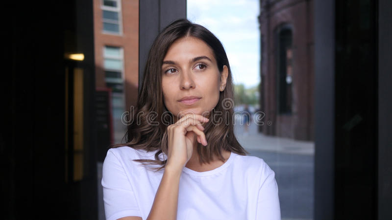 Thinking Pensive Beautiful Girl Standing in front of office stock photo