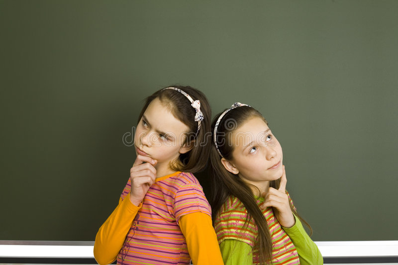 Thinking pupils. Two girls (11-13yo) are standing and thinking. There's blank greenboard behind them royalty free stock image