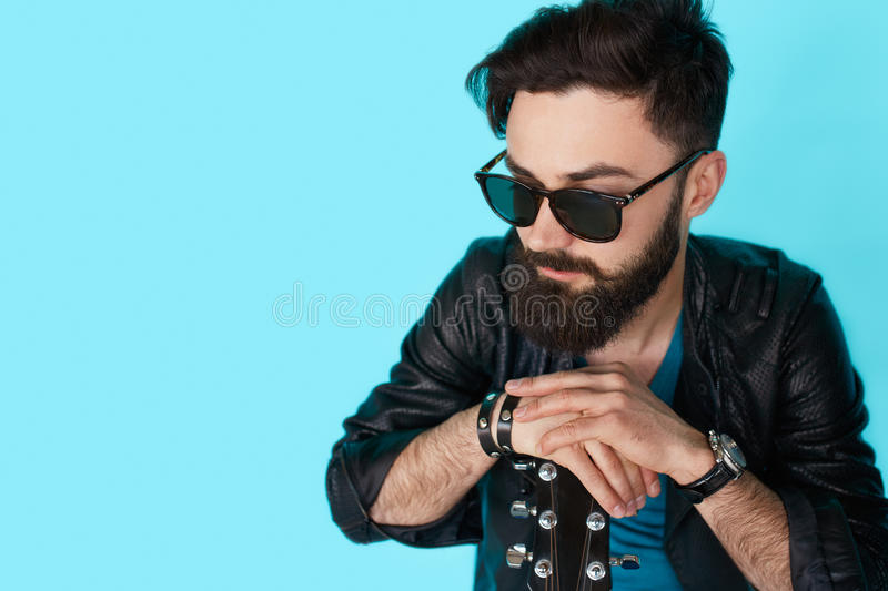 Thinking rock guitar player on blue background stock photos