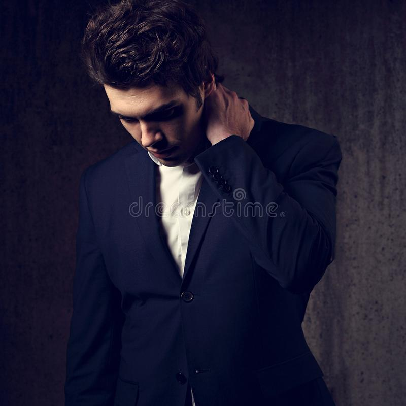 Thinking serious handsome business man looking down in black fashion suit and white style shirt on dark shadow background. Art. T royalty free stock photo