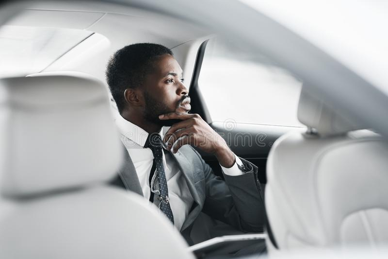 Thinking about solutions. Thoughtful businessman sitting in car royalty free stock photo