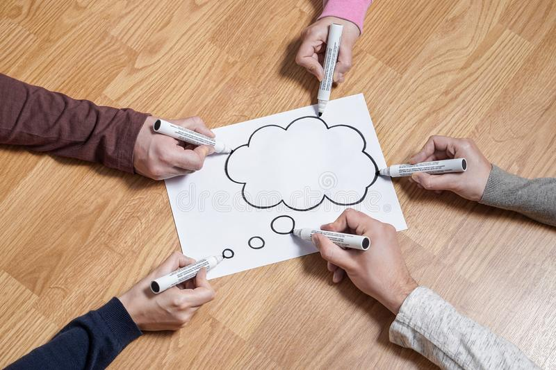 Thinking speech bubble balloon and thought cloud. Brainstorming new ideas together for marketing plan or school project. Teamwork, synergy and education. Group royalty free stock photo